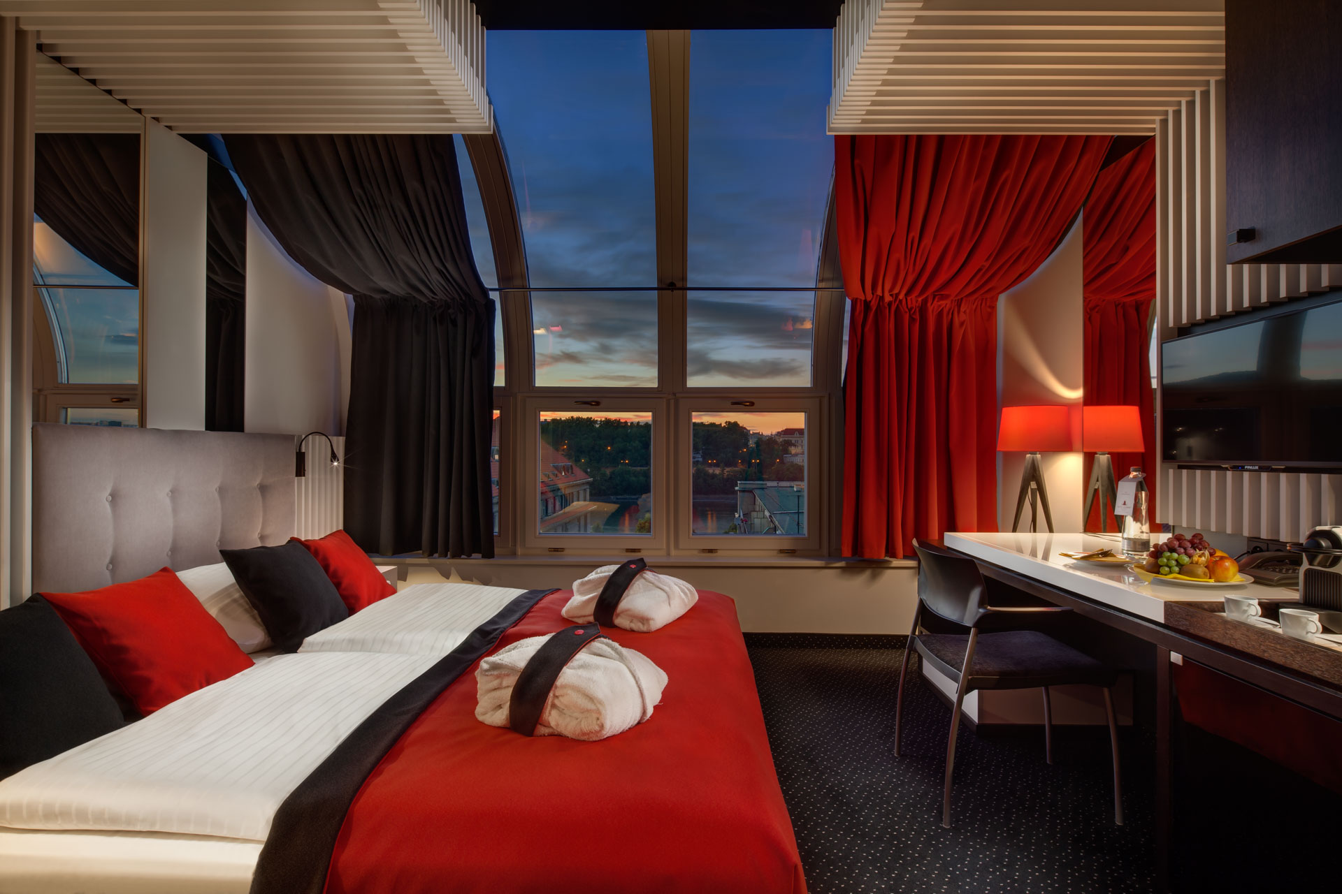 View on deluxe room with panorama windows showing a sunset sky at Hotel Clement Prague